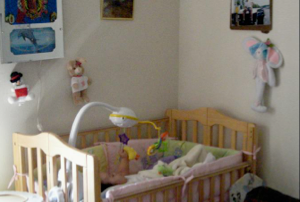 Photo 1:  Note the infant boy lying in his crib and that this apartment is neat and clean as described in the story.